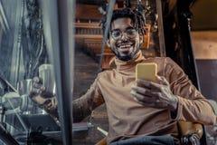 Positiv förtjust brunettman som ser hans grej fotografering för bildbyråer