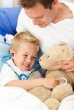 Positiv fader och hans sjuka leka för son Arkivfoton