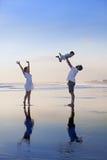 Positiv familj som har gyckel på den svarta sandhavsstranden Fotografering för Bildbyråer