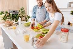 Positiv flicka och hennes fadermatlagningsallad tillsammans arkivbild
