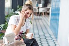 Positiv flicka som dricker kaffe royaltyfri foto