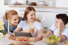 Positiv flicka som vilar med hennes moder och broder i köket royaltyfri foto