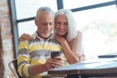 Positiv gealterte Paare unter Verwendung ihres intelligenten Telefons lizenzfreie stockbilder