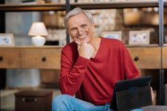 Positiv gealterter Mann, der eine Tablette hält lizenzfreies stockbild