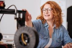Positiv glad kvinna som ser skrivaren 3D Arkivbild