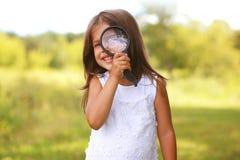 Positiv gladlynt liten flicka som ser till och med ett förstoringsglas Arkivbild