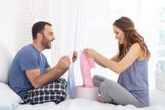 Positiv gravid kvinna och man som väljer crawlsimmare royaltyfri foto