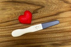 Positiv graviditetstest och en hjärta royaltyfri bild