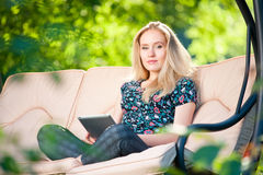 Positiv härlig ung kvinna som använder tableten Arkivfoto
