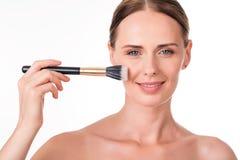 Positiv hållande makeupborste för ung kvinna Arkivfoto