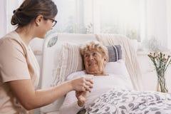 Positiv hög kvinna som ligger i säng, hjälpsam doktor i den beigea likformign som stöttar henne fotografering för bildbyråer