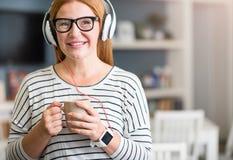 Positiv hög kvinna som lyssnar till musik royaltyfri fotografi