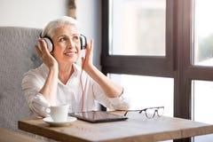 Positiv hög kvinna som lyssnar till musik royaltyfri bild