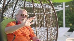 Positiv hög man som sitter på en hängande stol som kopplar av i hotellkomplexet Mannen som ger högt fem Vila i lager videofilmer