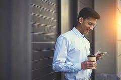 Positiv industudent i tillfälliga kläder som håller ögonen på den roliga videoen och messaging med vänner Arkivfoton