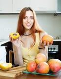 Positiv kvinna med den mogna mango i hem Royaltyfri Foto