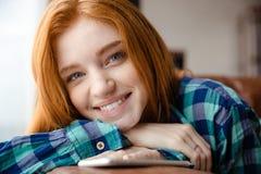 Positiv kvinna med rött hår som lyssnar till musik från mobiltelefonen Arkivbild