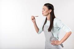 Positiv kvinna som är involverad i matlagning royaltyfri fotografi