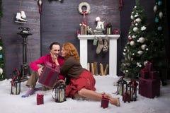 Positiv kvinna som är tacksam till hennes make för angenäm julgåva arkivfoton