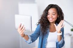Positiv kvinna som använder minnestavlan Arkivbild