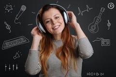 Positiv kvinna som känner sig bra, medan lyssna till älskvärd musik arkivfoton