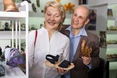 Positiv kvinna som väljer par av skor Royaltyfri Bild
