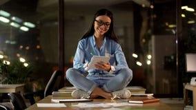 Positiv kvinnlig sittande lotusblomma poserar att skriva i anteckningsboken, modern arbetsmilj? royaltyfria bilder