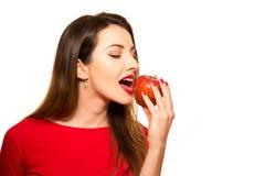 Positiv kvinnlig som biter en stor röd Apple frukt som ler på vita lodisar Royaltyfri Bild