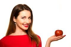Positiv kvinnlig som biter en stor röd Apple frukt som ler på vita lodisar Royaltyfri Foto