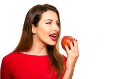 Positiv kvinnlig som biter en stor röd Apple frukt som ler på vita lodisar Royaltyfria Foton