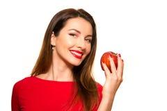 Positiv kvinnlig som biter en stor röd Apple frukt som ler på vita lodisar Arkivbild