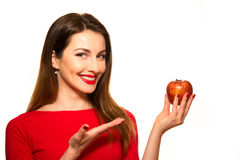 Positiv kvinnlig som biter en stor röd Apple frukt som ler på vita lodisar Arkivbilder