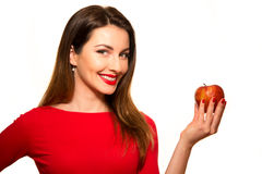 Positiv kvinnlig som biter en stor röd Apple frukt som ler på vita lodisar Royaltyfria Bilder