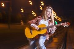 Positiv-lächelnde kaukasische blonde Frau, welche die Gitarre spielt Stockfoto