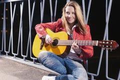 Positiv-lächelnde kaukasische blonde Frau, welche draußen die Gitarre an der Dämmerung spielt Lizenzfreies Stockbild