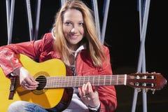 Positiv-lächelnde kaukasische blonde Frau, welche draußen die Gitarre an der Dämmerung spielt Mischung des Blitz-und Halogen-Lich Stockfotos