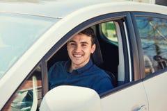 Positiv le chauff?r f?r ung man som sitter bak styrhjulet som k?r hans splitterny bil arkivbild