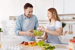 Positiv le fader och dotter som har gyckel i köket arkivbilder
