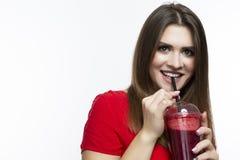 Positiv le flicka som dricker den röda smoothien Juice Mix fotografering för bildbyråer