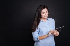 Positiv le kvinna som använder den moderna minnestavlan Arkivbild