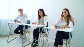 Positiv le man och kvinnliga studenter som svarar fråga och att utföra kommunikationsexpertis arkivfilmer