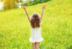 Positiv lockig liten flicka som tycker om solig dag för sommar och att ha gyckel Arkivfoto