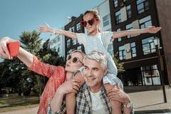 Positiv lycklig familj som tillsammans tar en selfie arkivbild