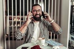 Positiv lycklig man som sätter telefoner till hans öron arkivbild