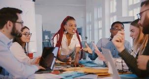 Positiv lycklig svart affärskvinna som arbetar samman med olika kollegor i det moderna moderiktiga kontoret, sund arbetsplats arkivfilmer