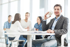 Positiv man som dricker kaffe Fotografering för Bildbyråer