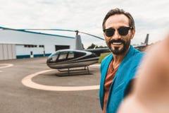 Positiv man som tar selfies med helikoptern och le fotografering för bildbyråer