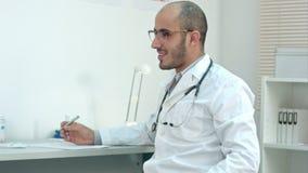 Positiv manlig doktor i regeringsställning som talar till patienten stock video