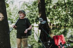Positiv manlig fisher som rymmer yrkesmässig fiska utrustning arkivbild