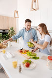 Positiv manmatlagning med hans dotter i köket royaltyfri fotografi